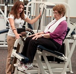 Fitness Center instructor working with woman lifting weights