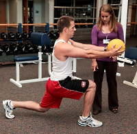 Sports Medicine Fitness Center member lunging with medicine ball