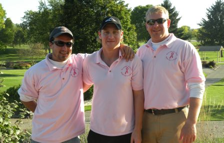 Three golfers wearing pink shirts