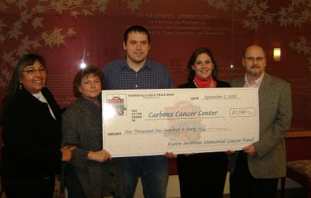 Group posing with a large check