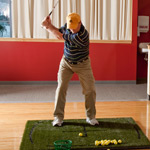 A golfer hits balls into a net in the UW Health Golf Clinic