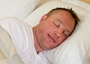 A man relishing the contentment of a good night's sleep