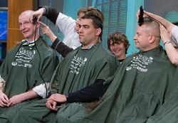 Three doctors getting their head shaved