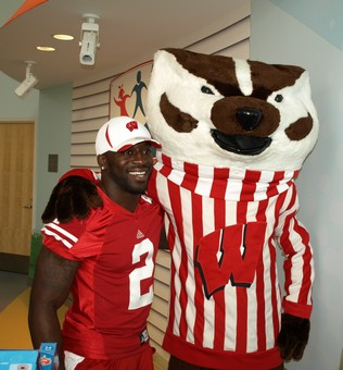 UW senior defensive back Jay Valai and Bucky Badger are all smiles before leaving to hand out toys and meet patients.