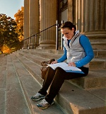 College student reading a book on library stairs