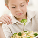 Boy eating broccoli