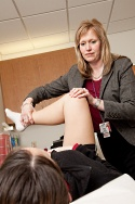 UW Health Sports Medicine physician services for runners: Doctor working on runner