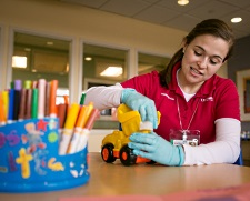 American Family Children's Hospital volunteer cleaning toys.