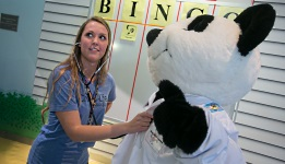 American Family Children's Hospital Child Life therapist taking a fake bear's heartbeat at BINGO.
