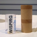 The current choke-test cylinder used by the CPSC next to an empty toliet-paper roll, which is recommended by USPIRG