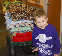 Emerson Koch helps transport some of the hand-made blankets donated to the PICU.