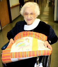 101-year-old Eva shows off a quilt she helped make through Project Linus.