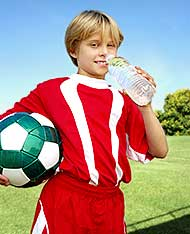 Boy drinking from water bottle during soccer game