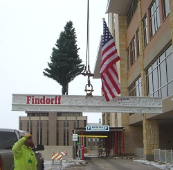 A Findorff employee oversees the raising of the topping off tree at American Family Children's Hospital.