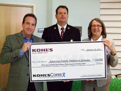 Todd Pralle, manager of the Madison West Kohl's Department Store, presents a check to Nan Peterson of American Family Children's Hospital for $114,092, along with Madison Fire Department Chief Steven Davis.