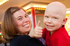 Austin and his mother give a thumbs up to the Champions for Kids Radiothon at American Family Children's Hospital