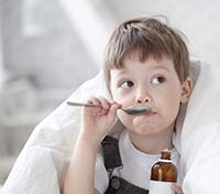American Family Children's Hospital Pediatric Diabetes: young boy taking cough syrup