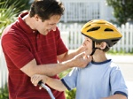 Dad helping son with bike helmet