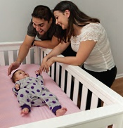 American Family Children's Hospital Safety Center: Two parents and a child in a crib
