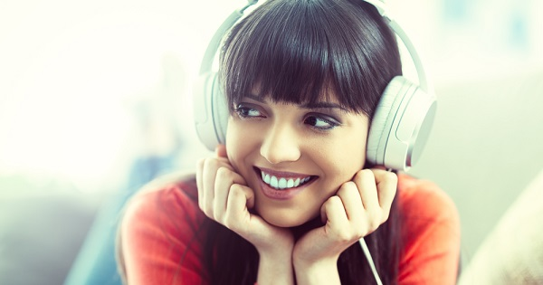 Young woman listening on headphones; Research has shown that music does have a positive influence on individuals