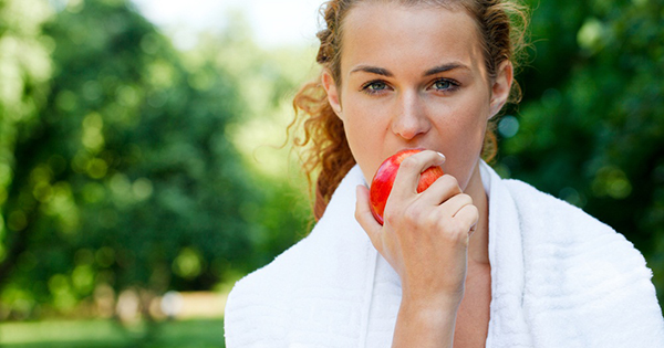 Fit woman eating apple; Snacks can play an important role for helping athletes stay energized