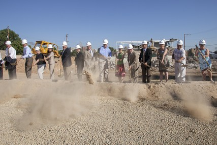 A group of dignitaries throw ceremonial shovels full of dirt at the groundbreaking.