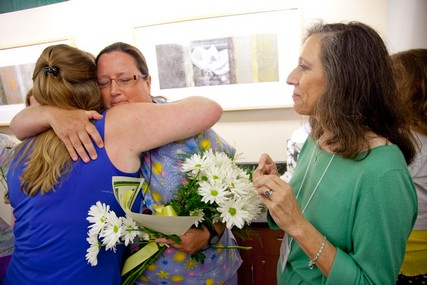 DAISY Award winner Gail Hettrick gets a hug from a fellow finalist while Bonnie Barnes looks on.