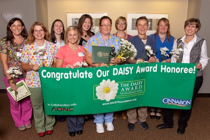 The finalists with the DAISY Award banner - it will be displayed in the work area of the current honoree.