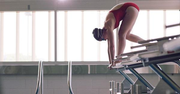 Swimming for exercise: Woman in starting blocks at the pool