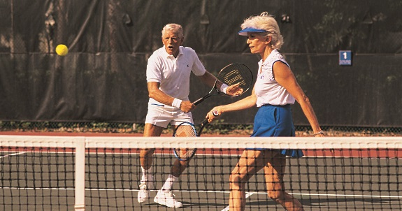 Two older people playing tennis