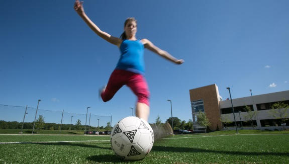 UW Health Sports Medicine ACL training programs: Woman kicking a soccer ball