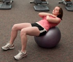Woman doing sit-ups on an exercise ball