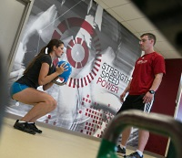 UW Health Sports Performance runners strength training: Runner doing squats with a coach