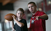 UW Health Sports Performance football training: Boy throwing a football with trainer