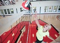 UW Health Sports Performance Preseason volleyball training: Girl hitting a volleyball at the net