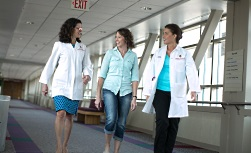 University Hospital patient guide: Two doctors and patient walking in the hall
