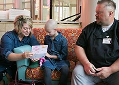 Josie and her mother, Jessica, read the card given to Josie on her last day of radiation treatment by Dan O'Kane, a cook in the Farmers' Market Cafe