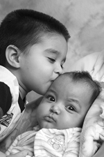 Alfredo kisses his little sister Emily during their Flashes of Hope photo shoot, American Family Children's Hospital, Madison, Wisconsin