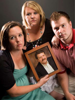 The Howell Family with a picture of their father