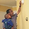 Man with his son, installing a smoke detector