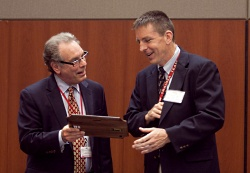Dr. Gerald Lang accepts his excellence award from UW Medical Foundation president and CEO Jeffrey Grossman, MD.
