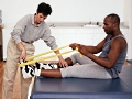 Athletic trainer working with a patient on rehabilitation exercises