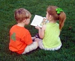 Two kids reading, enjoying the splendor of the grass