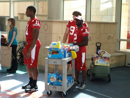UW football players David Gilbert (11), Patrick Butrym and Jay Valai (2) bring in some of the toys for patients.