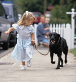 A young girl walking with her dog