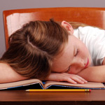 Girl sleeping on homework
