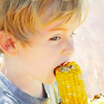 Boy eating corn