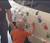 Austin Schuetz puts his print on the Hope On Wheels car.