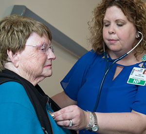 Laura Makarowski, RN, MSN, APNP, works with a patient in an assisted living facility, in a program that prevents residents from having to leave the facility to get primary care services