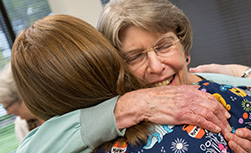 Marian Ehrenberg hugs a colleague at her birthday celebration